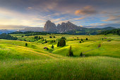 Amazing landscapes view of green hills with summer blue sky on sunrise from Seiser Alm Dolomites, Italy.