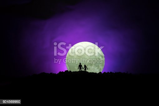 istock Amazing love scene. Silhouettes of young romantic couple standing under the moon light 924569950