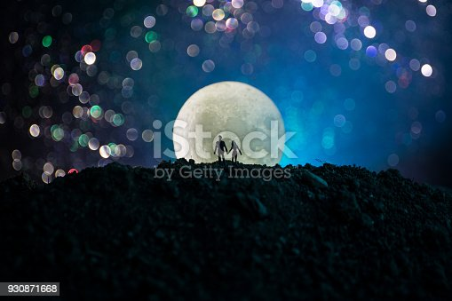 istock Amazing love scene. Silhouettes of young romantic couple standing under the moon light 930871668