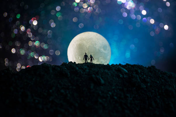 amazing love scene. silhouettes of young romantic couple standing under the moon light - romantic moon stock photos and pictures