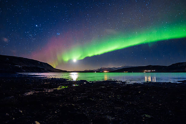Amazing Moonset and celestial Aurora Borealis in Iceland's winter sky A typical Nordic nightscape and very famous location for travelers and adventurers from all over the world - Iceland with the spectacular celestial lights Aurora Borealis above into the winter night sky and amazing partly reflected Northern lights and Moonset into the sea bed at low tide, which makes this Polar country popular spot for tourists willing to witness one of the greatest natural phenomenoms. Shot with Canon EOS 60D, wide 11mm angle lens, f2.8, ISO 3200, long exposure of 15 seconds. lenticular cloud stock pictures, royalty-free photos & images