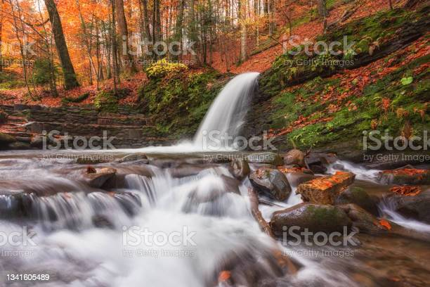 Photo of Amazing nature landscape with mountain waterfall in the dark colorful autumn forest, natural outdoor travel background suitable for wallpaper