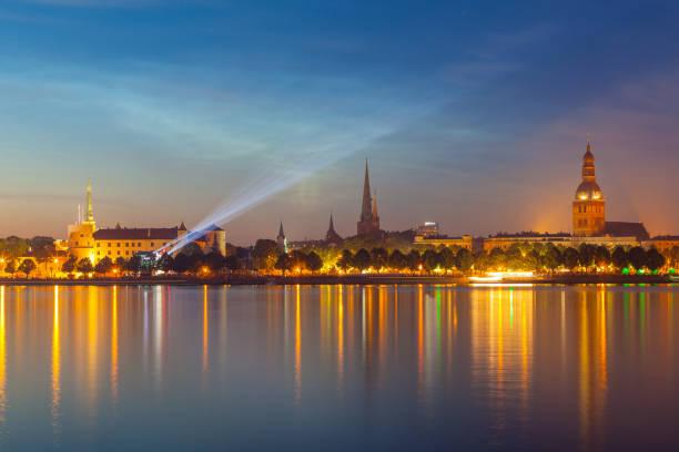 RIGA, LATVIA - 23 JUN 2016. Amazing night panorama of illuminated old town of Riga with reflection in Daugava river. Shortest night in a year, Ligo festival stock photo