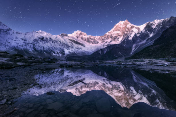 Amazing night scene with himalayan mountains and mountain lake at starry night in Nepal. Landscape with high rocks with snowy peak and sky with stars reflected in water. Beautiful Manaslu, Himalayas Amazing night scene with himalayan mountains and mountain lake at starry night in Nepal. Landscape with high rocks with snowy peak and sky with stars reflected in water. Beautiful Manaslu, Himalayas reflection lake stock pictures, royalty-free photos & images