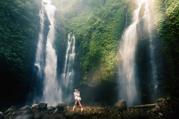 Amazing romantic view of happy couple near beautiful grand waterfall Amazing romantic view of happy couple near beautiful grand waterfall in jungles mountain. A man making proposal to his girlfriend. Success life. Marriage couple outdoor honeymoon stock pictures, royalty-free photos & images