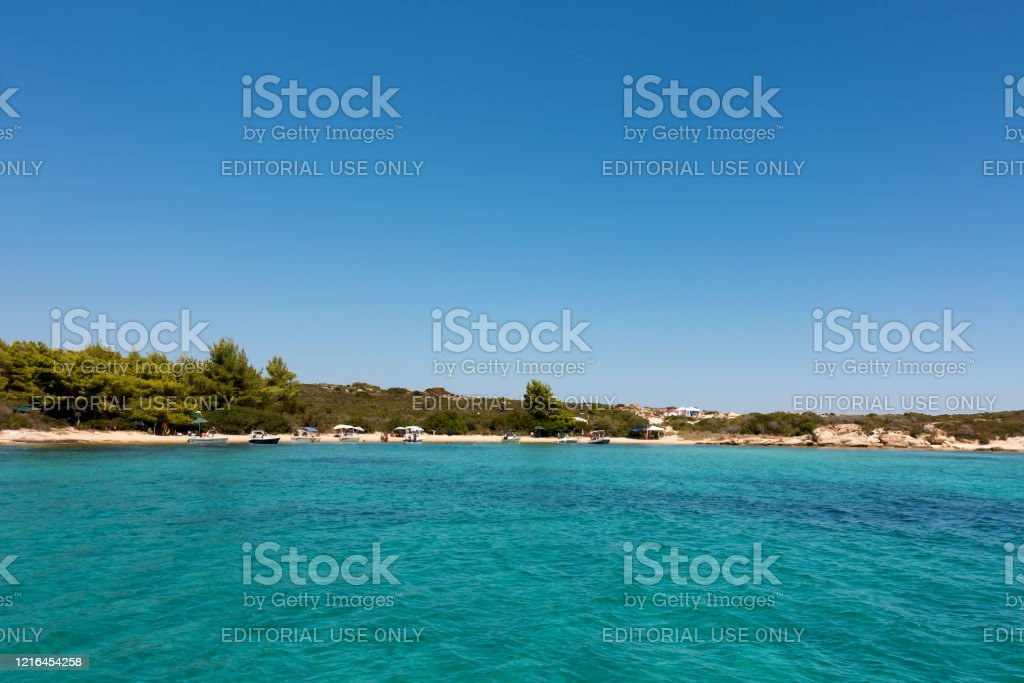Amazing scenery by the sea in Diaporos island, Sithonia, Halkidiki, Greece August 8th 2019 - Chalkidiki, Greece - Amazing scenery by the sea in Diaporos island, Sithonia, Chalkidiki, Greece, with people enjoying the beach Absence Stock Photo
