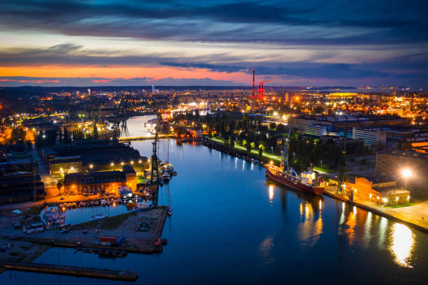 amazing scenery of the shipyard and canals of gdansk at dusk - drone shipyard night imagens e fotografias de stock