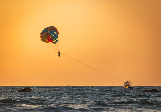 amazing shot at sunset of Parasailing water amusement Indian water sports in north Goa  flying on a parachute behind a boat on a summer holiday by the sea in the resort Baga beach Goa India goa stock pictures, royalty-free photos & images