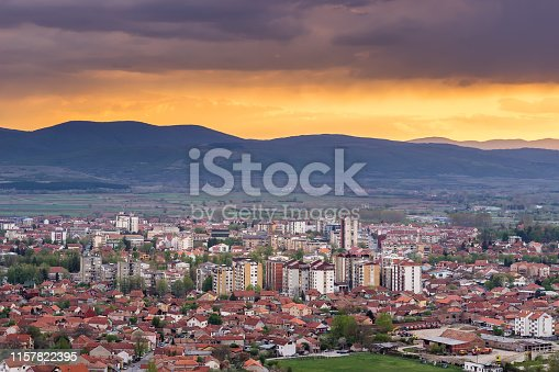 Stunning golden hour sky over colorful downtown of Pirot cityscape with dramatic clouds and horizon mountains in the distance