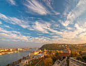 Amazing sky with picturesque clouds over Danube river and Buda hills in the central area of Budapest, Hungary. Castle gate tower, Danube embankment, Citadella and Gellert Hill on foreground