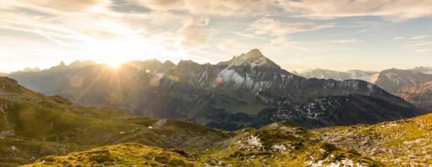 wunderbaren sonnenaufgang in den bergen. schöne lens-flares und sonnenstrahlen - allgäu stock-fotos und bilder