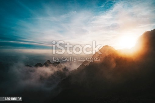 Amazing sunrise view from Mountains. sun sets behind the mountain. View from the top of a high mountain to the valley covered with clouds. Silhouettes of mountain peaks in fog in bright sunlight.
