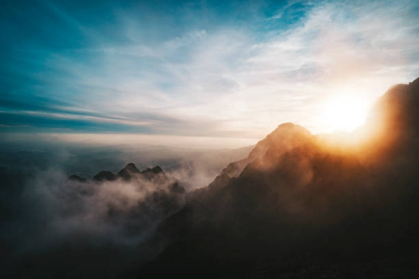 Amazing sunrise view from Mountains. sun sets behind the mountain. View from the top of a high mountain to valley covered with clouds. Silhouettes of mountain peaks in fog in bright sunlight. stock photo