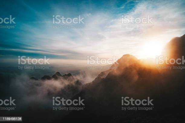 Photo of Amazing sunrise view from Mountains. sun sets behind the mountain. View from the top of a high mountain to valley covered with clouds. Silhouettes of mountain peaks in fog in bright sunlight.