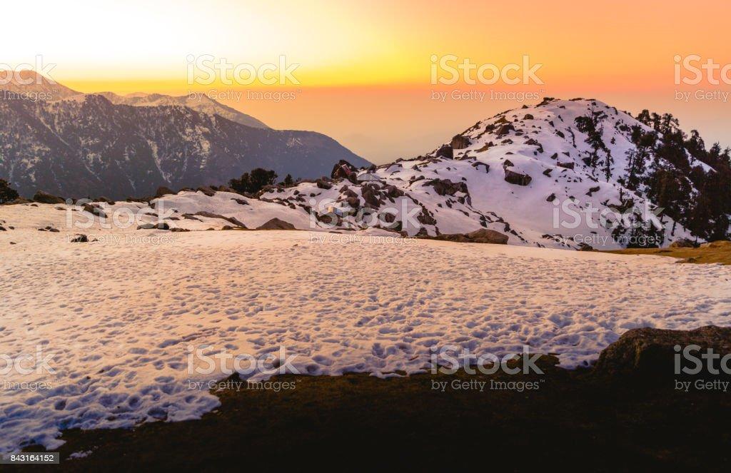 Amazing sunset at Triund, Mcleod ganj, Dharamsala, himachal pradesh, India. Yellow orange purple and golden light scene around dusk, sunset. snow mountains in cold winter. Camping at night stock photo