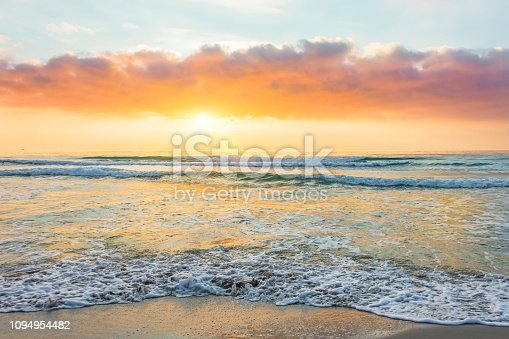 istock Amazing sunset on a sandy beach of an island in the ocean. 1094954482