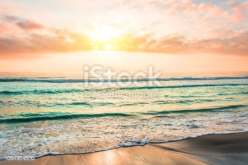 istock Amazing sunset on a sandy beach of an island in the ocean. 1094954520