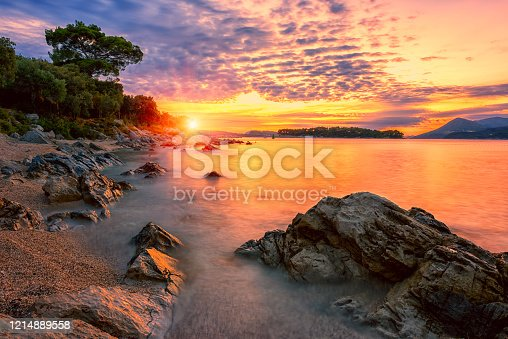 Amazing sunset seascape, beauty of nature. Scenic view of the sea, rocky seacoast and sandy beach, golden colored sky and sun, outdoor travel background, Croatia