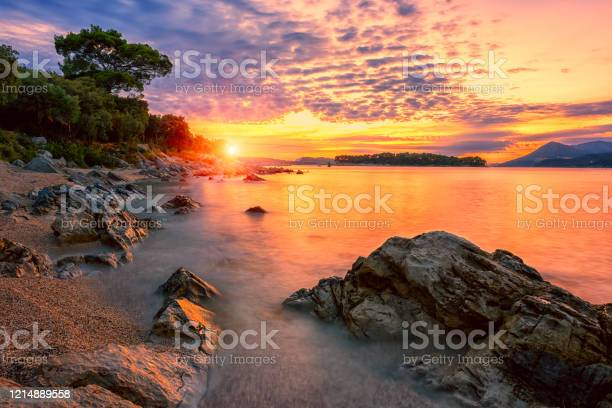 Photo of Amazing sunset seascape, beauty of nature. Scenic view of the sea, rocky seacoast and sandy beach, golden colored sky and sun, outdoor travel