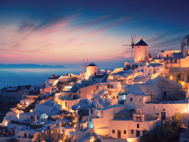 Amazing sunset view with white houses in Oia village on Santorini island in Greece. stock photo