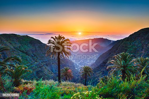 istock Amazing tropical scenery with palm trees and mountains at sunset 663909890