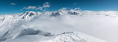 Majestic snowcapped mountains looking through the clouds in France (Val Thorens). View from Cime Caron (3200m).