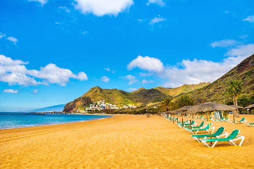 Amazing view of beach las Teresitas with yellow sand, umbrellas, longues and palm trees. Location: Santa Cruz de Tenerife, Tenerife, Canary Islands. Artistic picture. Beauty world.
