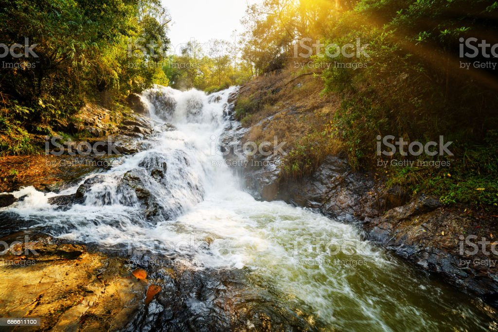 Amazing view of natural waterfall among green woods at sunset stock photo