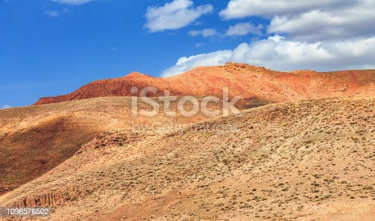 istock Amazing view of sandy desert at high Atlas mountains range. Moroccan landscapes with bright sun and clear blue sky. View of the desolating valley mountains. Beautiful Northern African Landscape . Fascinating view from the hill to the valley in Morocco 1096576502