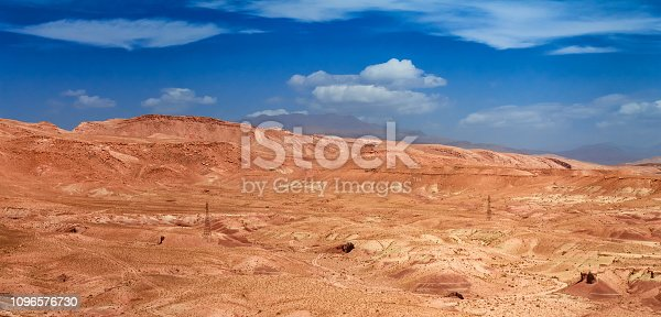 istock Amazing view of sandy desert at high Atlas mountains range. Moroccan landscapes with bright sun and clear blue sky. View of the desolating valley mountains. Beautiful Northern African Landscape . Fascinating view from the hill to the valley in Morocco 1096576730