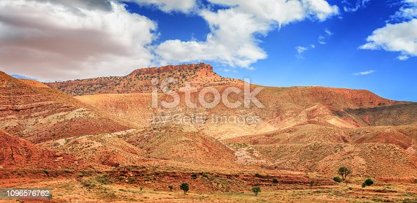 istock Amazing view of sandy desert at high Atlas mountains range. Moroccan landscapes with bright sun and clear blue sky. View of the desolating valley mountains. Beautiful Northern African Landscape . Fascinating view from the hill to the valley in Morocco 1096576762