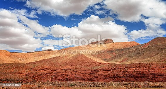 istock Amazing view of sandy desert at high Atlas mountains range. Moroccan landscapes with bright sun and clear blue sky. View of the desolating valley mountains. Beautiful Northern African Landscape . Fascinating view from the hill to the valley in Morocco 1096576860