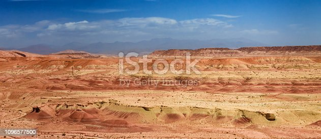 istock Amazing view of sandy desert at high Atlas mountains range. Moroccan landscapes with bright sun and clear blue sky. View of the desolating valley mountains. Beautiful Northern African Landscape . Fascinating view from the hill to the valley in Morocco 1096577500
