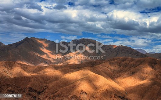 istock Amazing view of sandy desert at high Atlas mountains range. Moroccan landscapes with bright sun and clear blue sky. View of the desolating valley mountains. Beautiful Northern African Landscape . Fascinating view from the hill to the valley in Morocco 1096578154