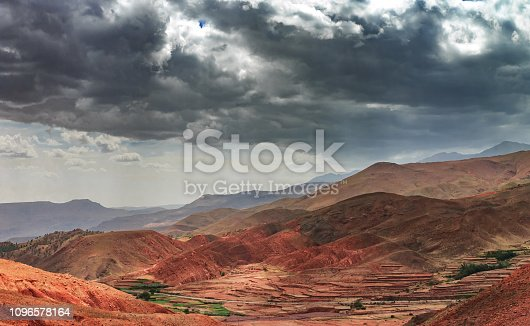istock Amazing view of sandy desert at high Atlas mountains range. Moroccan landscapes with bright sun and clear blue sky. View of the desolating valley mountains. Beautiful Northern African Landscape . Fascinating view from the hill to the valley in Morocco 1096578164