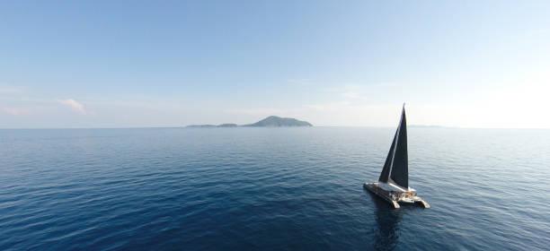 fantastisk utsikt till yacht segling på öppet hav vid blåsig dag. drönarvy - fåglar öga vinkel. - katamaran bildbanksfoton och bilder