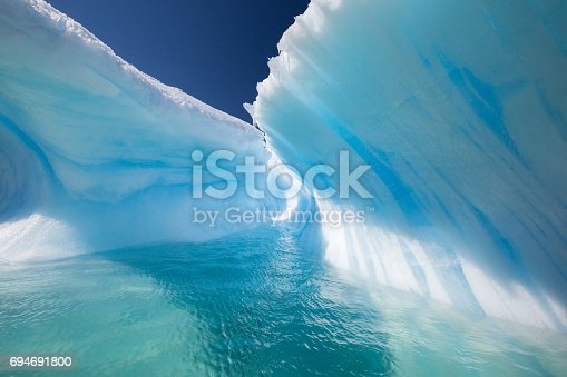istock Amazing Wave Shaped Iceberg with perfect blue tunnel 694691800
