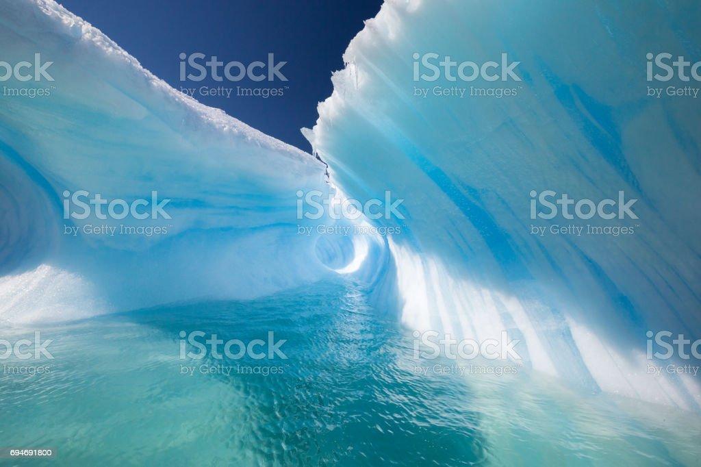Amazing Wave Shaped Iceberg with perfect blue tunnel stock photo