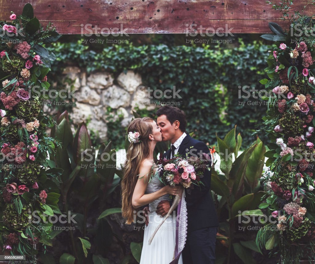 Amazing wedding ceremony with a lot of fresh flowers in Rustic style. Happy newlyweds kissing stock photo