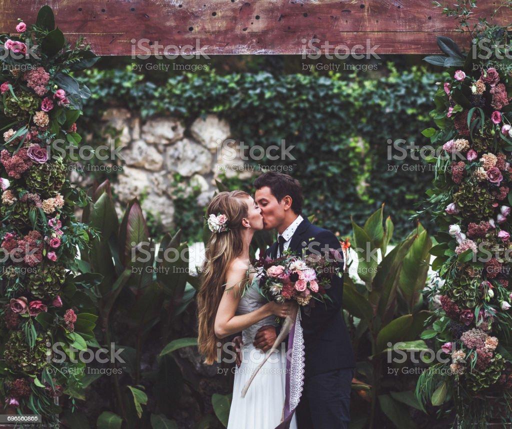 Cérémonie de mariage incroyable avec beaucoup de fleurs fraîches dans un style rustique. Heureux mariés s'embrassant - Photo