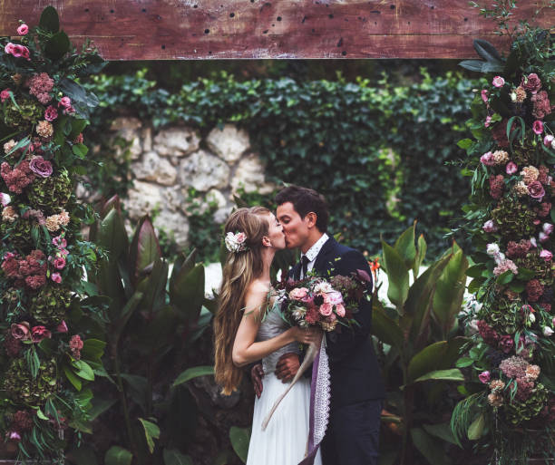 amazing wedding ceremony with a lot of fresh flowers in rustic style. happy newlyweds kissing - wedding stock pictures, royalty-free photos & images