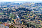 Amazing winter view of Chiesa di San Biagio, a small renaissance church in Montepulciano, Tuscany, Italy. Picturesque winter view of Tuscany with a church, colorful trees, fields and vineyards in Italy.