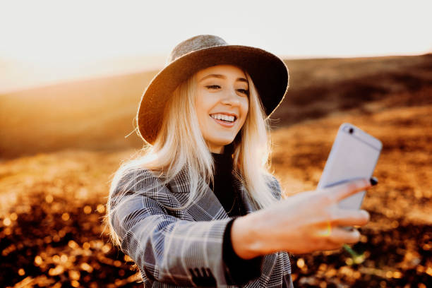 amazing woman with white hair dressed in suit and wearing hat doing a selfie smiling against beautiful landscape at the sunset. - phone, travelling, copy space imagens e fotografias de stock