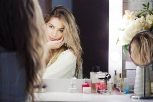 Increíble jovencita haciendo su maquillaje ante el espejo. Retrato de hermosa niña junto a la mesa de estética - foto de stock