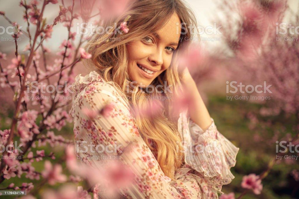 驚人的年輕女子擺在杏樹果園在春天 - 免版稅20多歲圖庫照片
