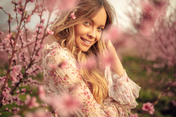Amazing young woman posing in apricot tree orchard at spring Portrait of amazing and beautiful young woman at spring in orchard of apricot trees in blossom. She is cheerful and happy, enjoying springtime. long hair stock pictures, royalty-free photos & images