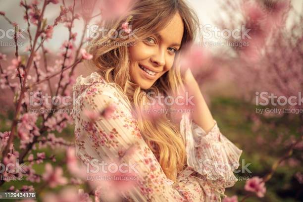 Photo of Amazing young woman posing in apricot tree orchard at spring