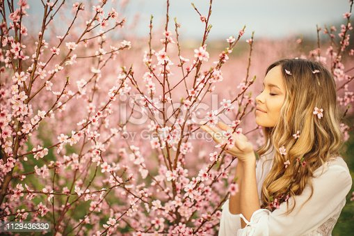 Portrait of amazing and beautiful young woman at spring in orchard of apricot trees in blossom. She is cheerful and happy, enjoying springtime.