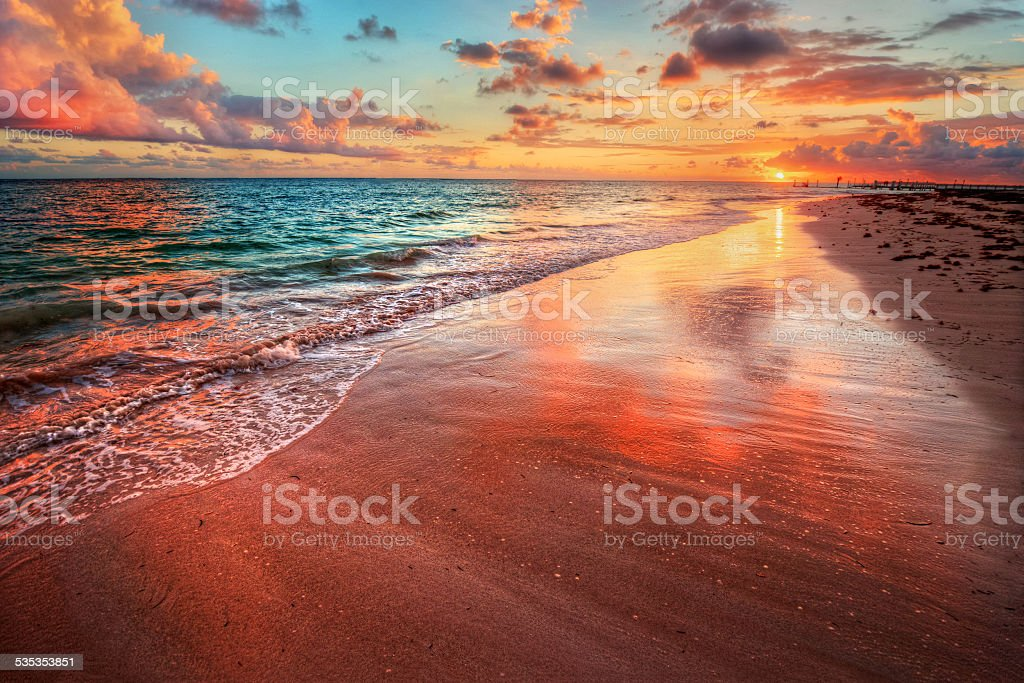 Amazingly colorful sea beach sunset with reflective red sand stock photo