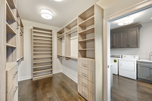 Walk-in closet with hardwood flooring connecting to laundry room